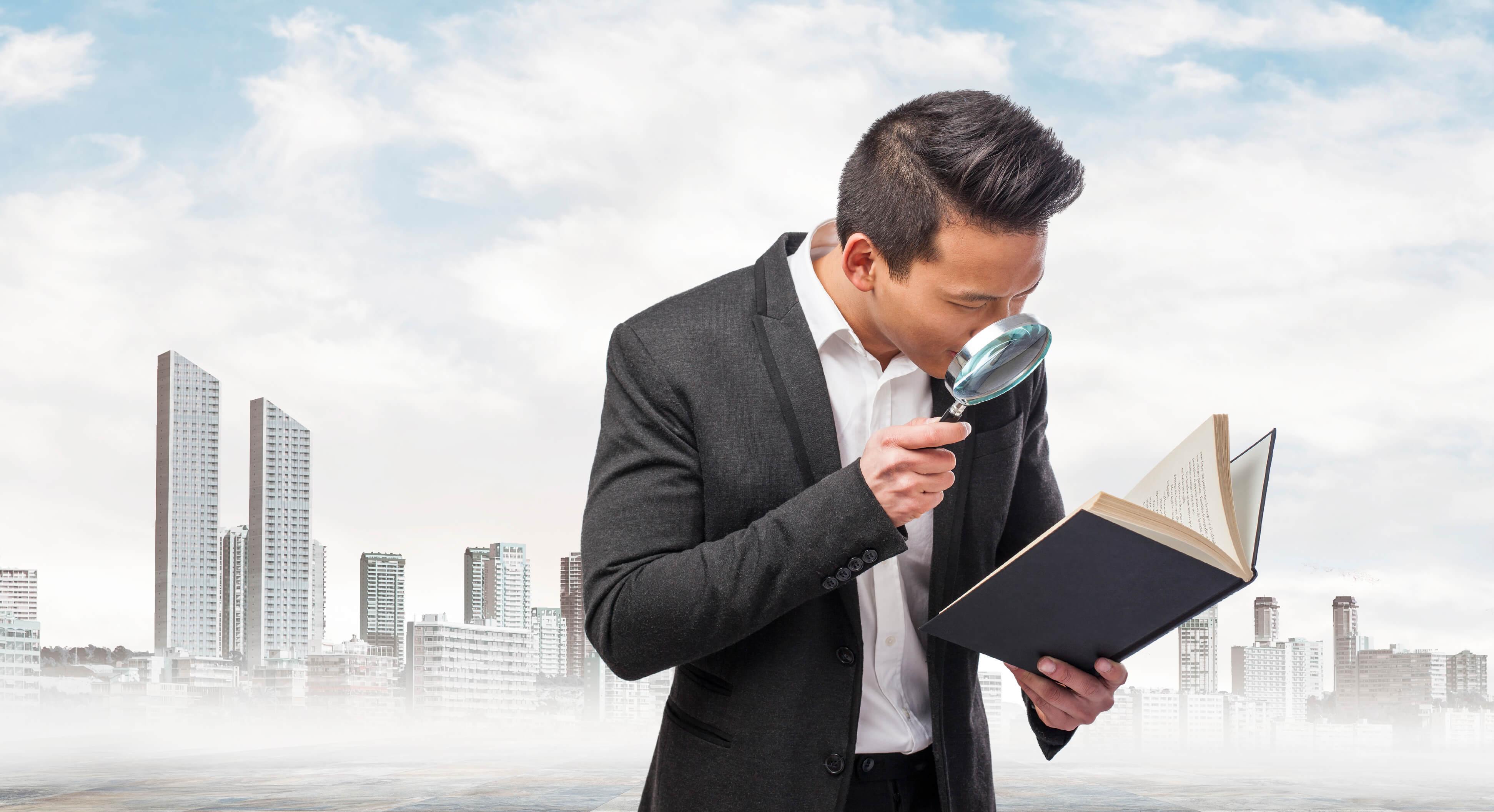 Homem com lupa observando livro