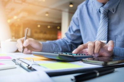 Homem de negócios com calculadora e caneta em mãos