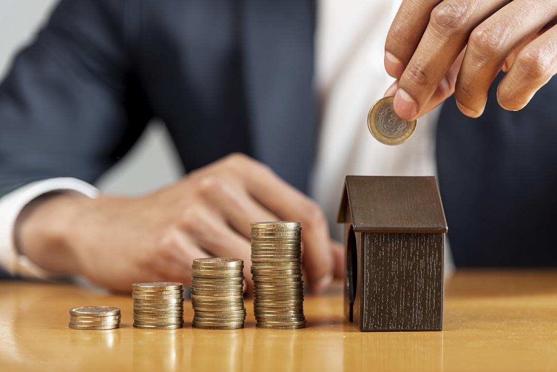 Construir para alugar - homem colocando dinheiro em uma miniatura de casa